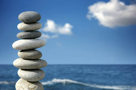 Photograph of a number of flat stones piled carefully onto another with a fantastic bright blue sky background at the seaside.
