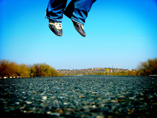 Shoes leaping leaping out of frame against a blue sky